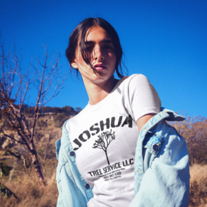 joshua-tree-service-t-shirt-a-woman-on-a-motorcycle-in-the-desert-the-secret-tours-joshua-tree-national-park-adventure-camping-climbing-hiking-white